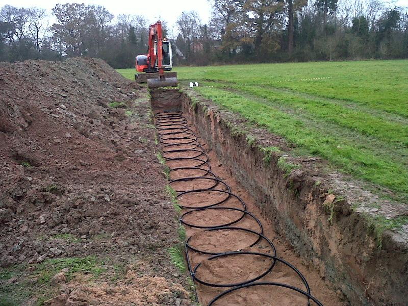 Ground Source Heat Pump Pipes Being Laid In A Trench